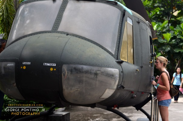 A curious tourist check out a Huey helicopter